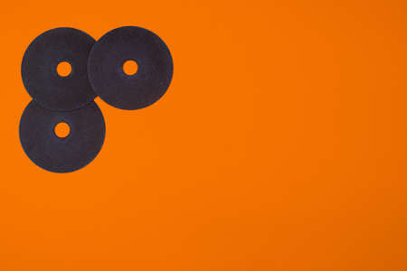 A cut-off wheel for a grinder tool on a orange background with a place for copyspace text. Tools for construction and repair, workshop.