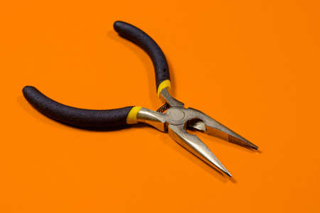 The round nose pliers on the orange background of copyspace. For electrician, jeweler and builder. Metal tool for bending wire and electrical wires