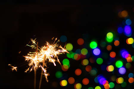 Sparkler on festive bokeh background. Festive greeting card for new year and christmas 2021, colorful lights in the background
