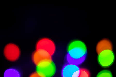 A brilliant glowing background side on black. The glitter light bokeh for the New Year and other holidays.