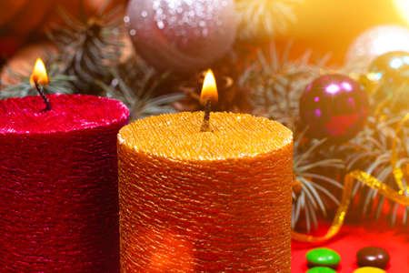 A beautiful Christmas image - a burning candle in gold color against the background of the Christmas tree. Romantic holiday photo with bokeh