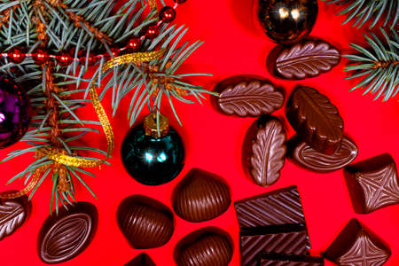 Pieces of chocolate and candy on a red New Years background with spruce branches and balls with a place for text. Sweet gifts for Christmas 写真素材