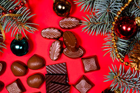 Pieces of chocolate and candy on a red New Year's background with spruce branches and balls with a place for text. Sweet gifts for Christmas.
