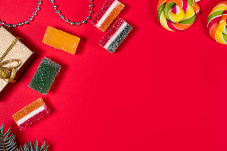 Marmalade candy and lollipops on a red New Years background. Banner for confectionery and candy store. With place for text.