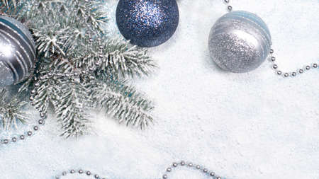 Spruce branch with Christmas toys and beads on a snow-covered white background with a place for copyspace text. A holiday card.