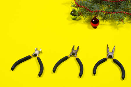 Construction tools pliers, rounds with a Christmas tree with a place to text on a yellow background. New Years banner for a construction store.