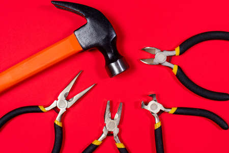 Construction tools hammer, pliers, cutters. tongs and round-the-heads on a red background. Banner for construction store and repair.