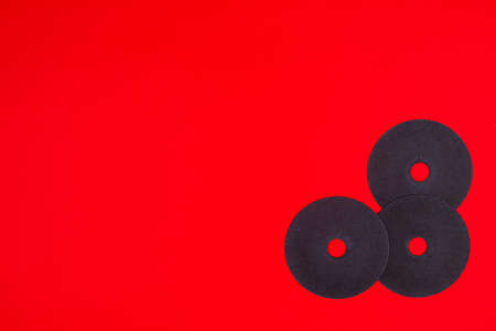 A cut-off wheel for a grinder tool on a red background with a place for copyspace text. Tools for construction and repair, workshop