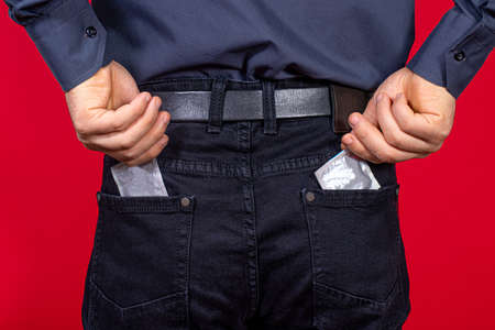 A man pulls out two condoms from his pocket. Barrier method of contraception, protected sex, prevention of unwanted pregnancy.
