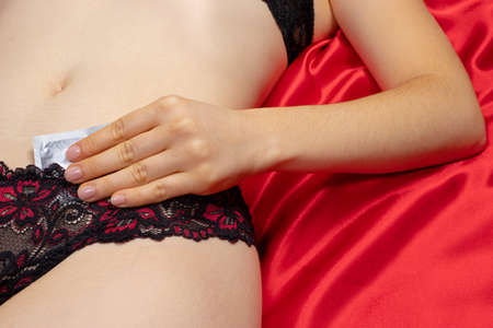 A beautiful sexy woman in lingerie holds a condom. Protected sex, barrier methods of contraception, protection against unwantedancies and sexually transmitted infections 版權商用圖片