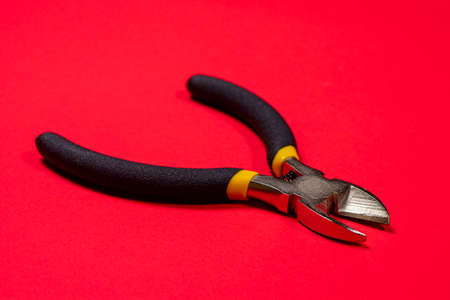 Nippers on a red background tool for cutting wires, cables and wire, for the electrician. The needle nose pliers.