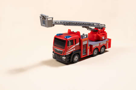 Toy typewriter on beige background red fire truck made of plastic. For the toy store, a gift for the boy.