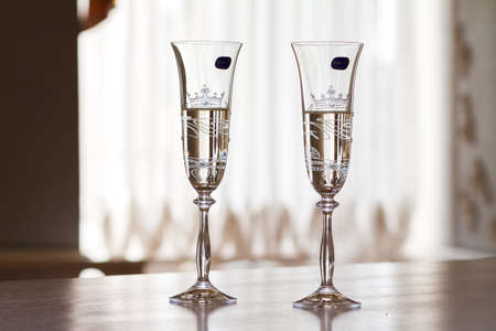Two wedding glasses with champagne in the registry office for the bride and groom in Ukraine on the table on the wedding day.