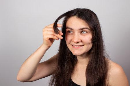 The girl shows the grown bangs. Hair care, long bangs. growing bangs.