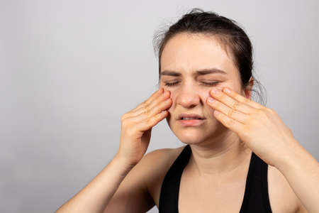 The woman holds her hands on the face - pain in sinuses, sinusitis perch and sinusitis, headache. With a place for copy space text. Stock Photo
