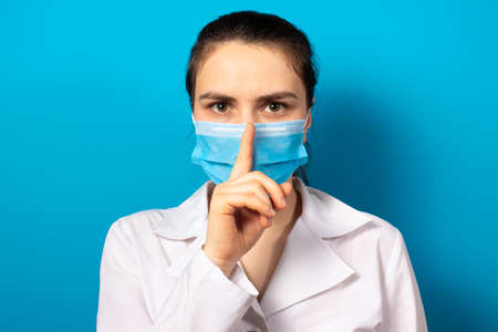The doctor in the mask shows a sign of silence finger at the mouth. Medical mystery in medicine and health care, medical error and secrets of new medical research. Medical secrecy.