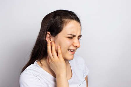 The woman has a sore ear - infection, inflammation from infection and otitis. Perforation ruptured the eardrum. Arthritis of the temporal lower jaw joint, osteoarthritis and pain in the jaw, mastoiditis.
