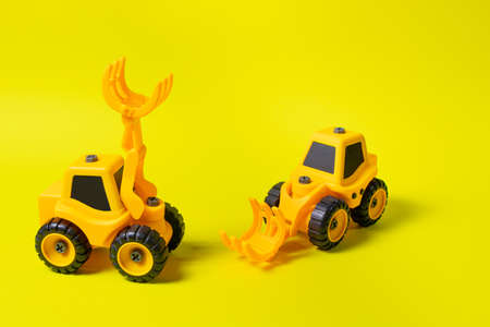 Two toy cars are yellow tractors of lumber loaders. Bright photo for the toy store