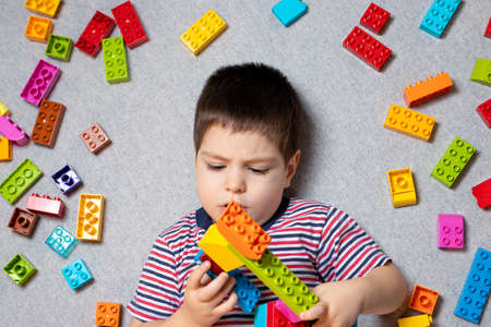 A boy of 3-4 years plays with multi-colored cubes block of designer on a gray background. Developing constructor toys for children, development. Beautiful bright photo for toy store. Banque d'images