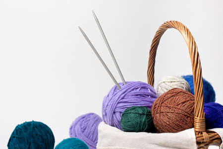 Wicker basket with colored balls of yarn for knitting or crocheting. Hobbies and recreation with needlework. On white background with place for text copy space. Stock Photo