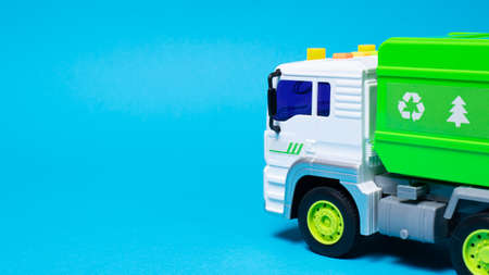 The toy is a garbage truck green with a white body on a blue background banner with a place for text for a toy store. Children's toys typewriter