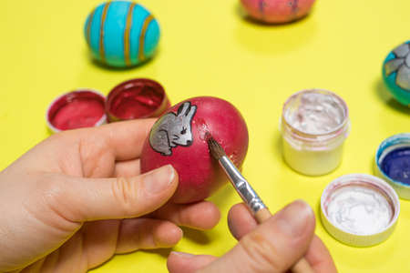 A woman paints a chicken egg with gouache paints with a brush on a yellow background. Easter photo, preparation for the holiday.