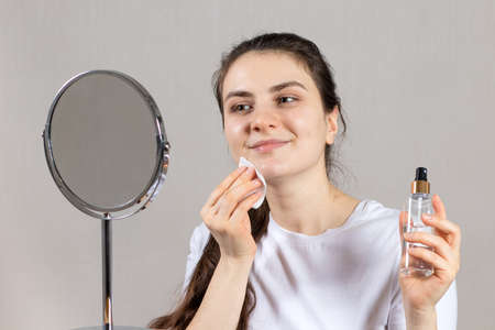 A 25-year-old woman holds a face and neck tonic and a cotton pad. Anti-wrinkle skin care, vitamins and acids for the face