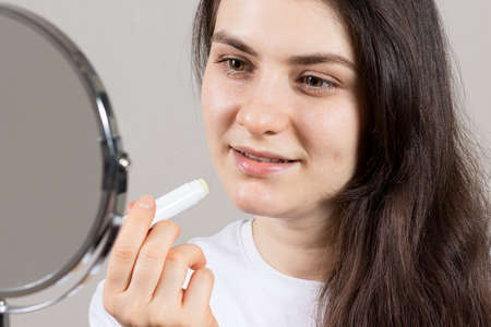 A woman paints her lips with a therapeutic balm. Treatment of cracks and dry lips, weathered lips.