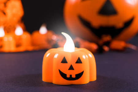 Halloween card - a candle in the form of a pumpkin glows against a dark background. Congratulations on the holiday.