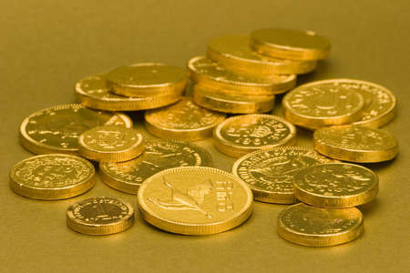 Gold Chocolate Coins set against a gold background. Stock Photo - 675836