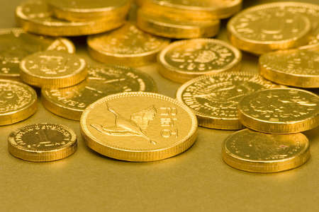 Gold Chocolate Coins set against a gold background. Stock Photo - 675837