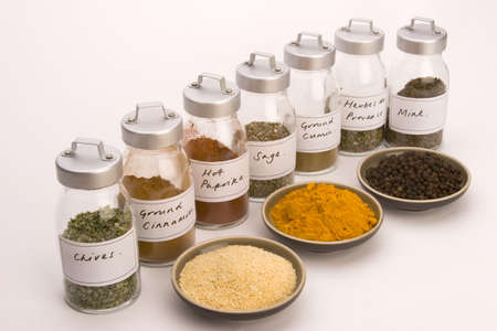Spice Jars with Spice bowls against a plain background. Stock Photo