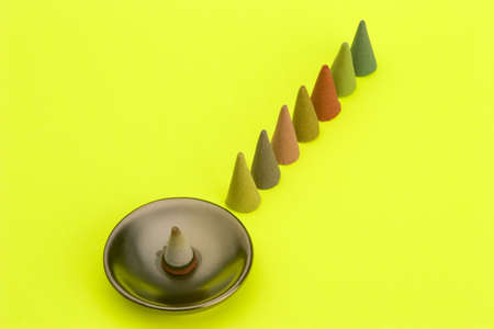 Multi coloured Incense cones against a bright coloured background. photo