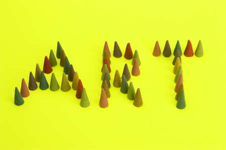Multi coloured Incense cones stating Art against a bright coloured background. photo