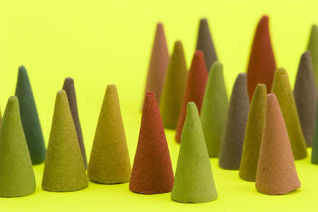 Multi coloured Incense cones against a bright coloured background.