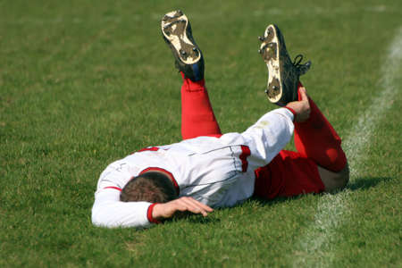 A football player injured, laying on the Pitch.