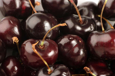 black cherry: Black Cherries in a bowl against a plain background. Stock Photo