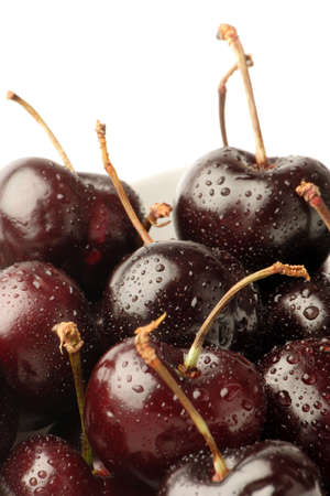 Black Cherries in a bowl against a plain background. Stock Photo