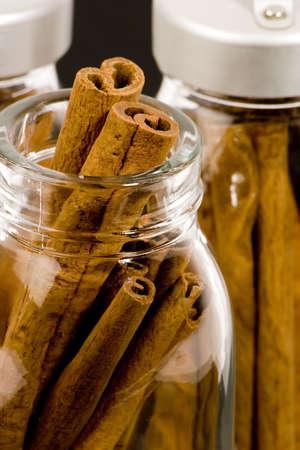 Cinnamon sticks in glass pots, studio shot, close up Stock Photo