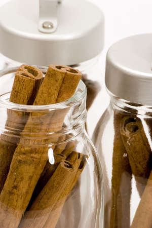 Cinnamon sticks in glass pots, studio shot, close up Stock Photo