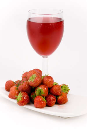 Ripe Strawberrys and glass of juice shot against a plain background. Stock Photo