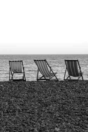 Deck chairs on the pebble beach of Beer, Devon.