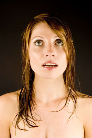 A young woman with a look of surprise against a plain background. Stock Photo