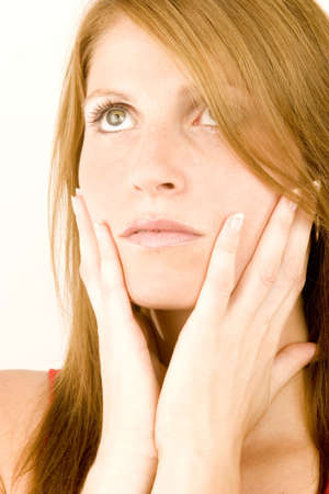A young woman deep in thought against a plain background.