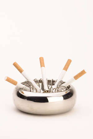 An ashtray with cigarettes against a plain background. photo