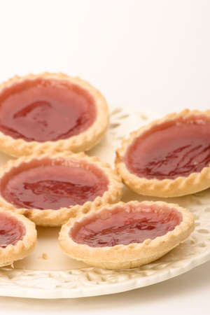 jam tarts: Strawberry Jam Tarts on a plate against a white background. Stock Photo
