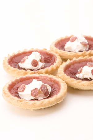 jam tarts: Strawberry Jam Tarts with cream against a white background.