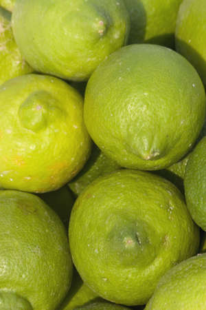 Green lemons arranged in a bowl next to a swimming pool Stock Photo - 942913
