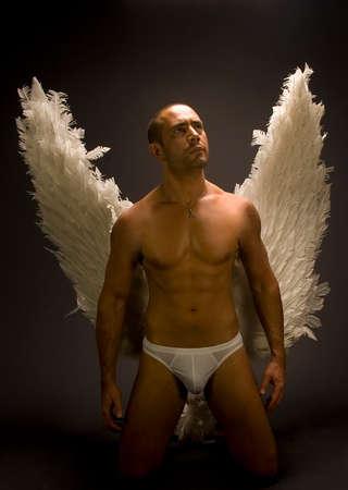 ange gardien: Un portrait d'un homme avec des ailes � plumes contre un fond sombre.  Banque d'images
