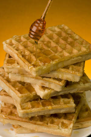 Multiple waffles with Honey against a coloured backgrond. Stock Photo